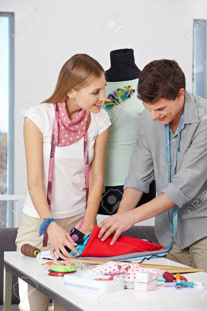 Two fashion designer with dress form looking through fabric Stock Photo - 15679652