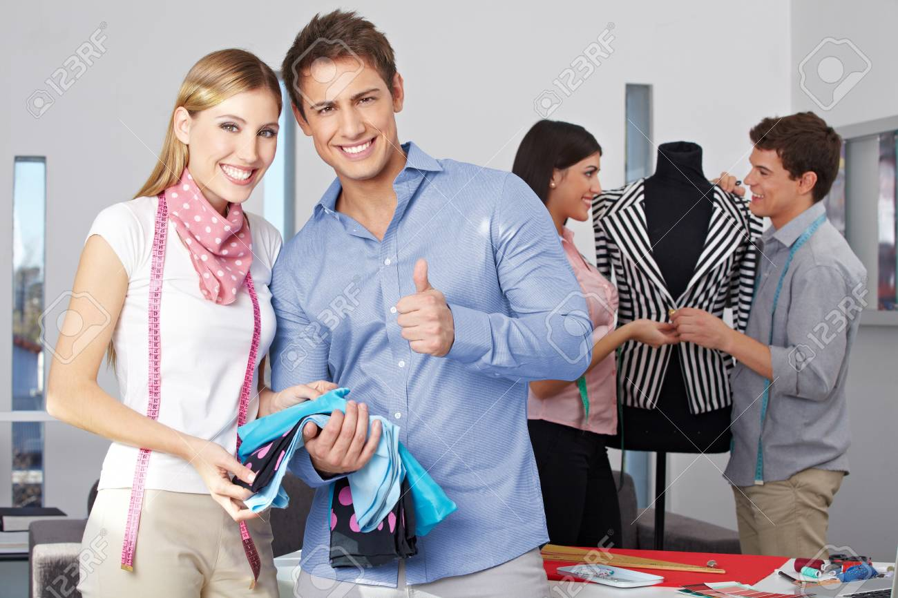 Fashion design student holding thumbs up with other people at work Stock Photo - 15679655