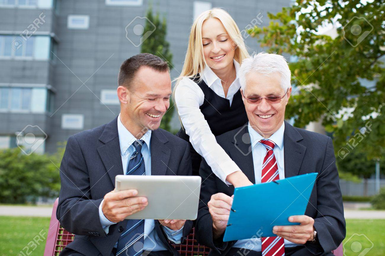 Smiling business people team working together in park Stock Photo - 15719311