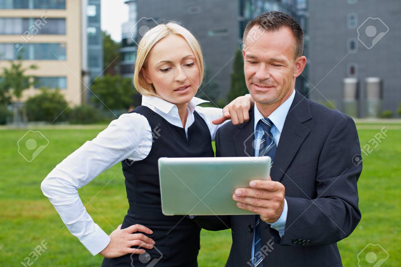 Business manager and assistant working with tablet PC outside Stock Photo - 15812751