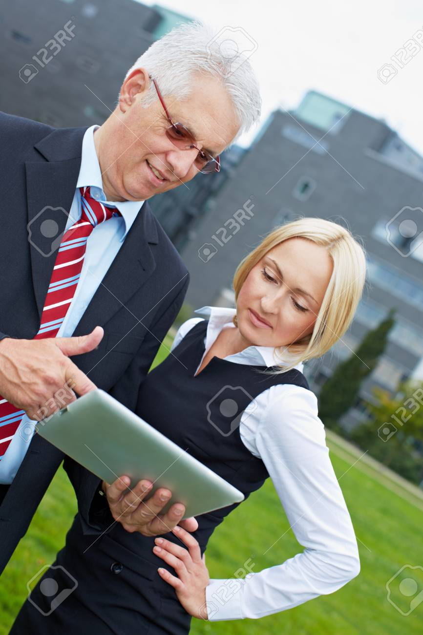 Tablet PC at a business meeting with two business people Stock Photo - 15812748