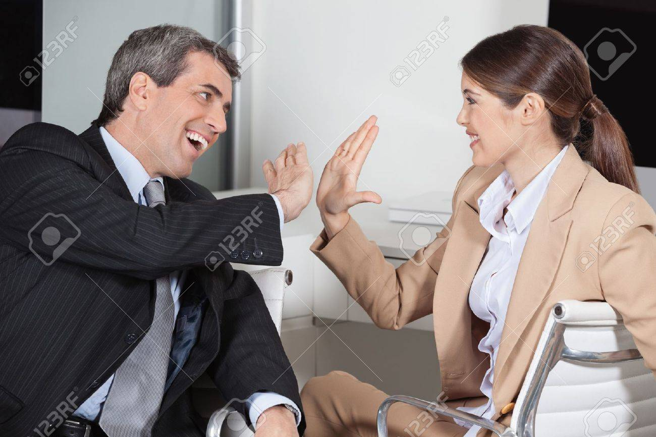 Manager and employee in the office giving high five to each other Stock Photo - 16128661