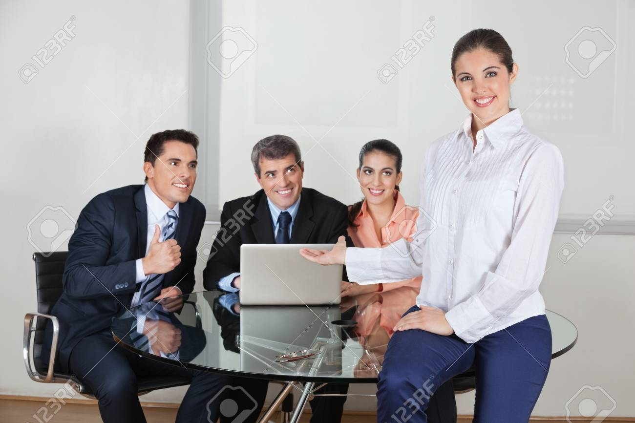 Smiling business woman presenting her office team with laptop computer Stock Photo - 16128634