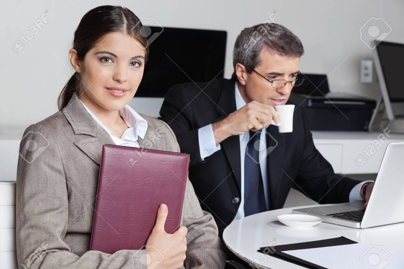 Assistent with datebook sitting near a businessman in the office Stock Photo - 16253765