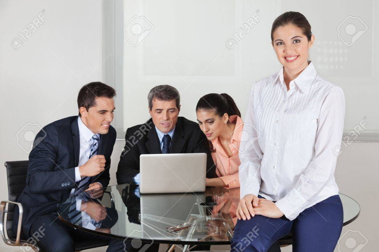 Happy attractive business woman with her team around a laptop in the office Stock Photo - 16253740