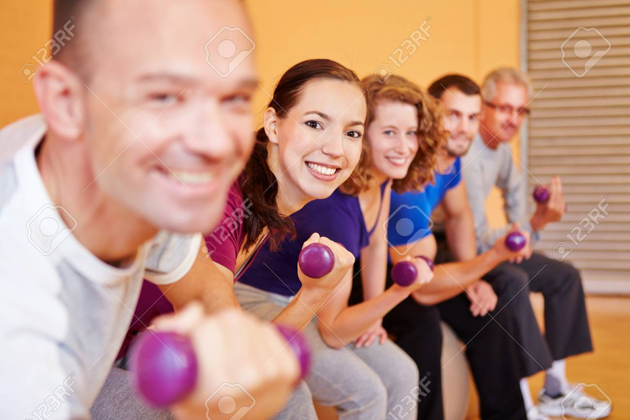 Happy group lifting dumbbells in a fitness center gym Stock Photo - 16490273