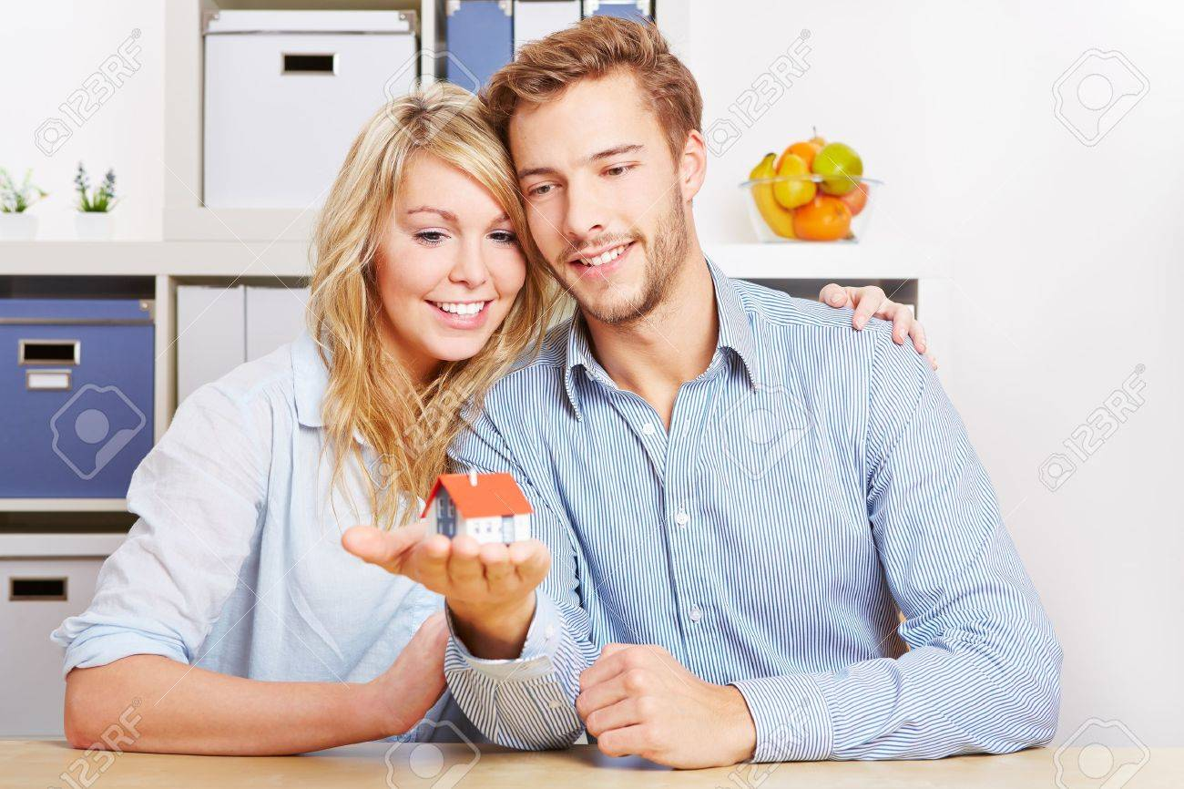 Smiling couple carrying a little home on the hands Stock Photo - 17104893