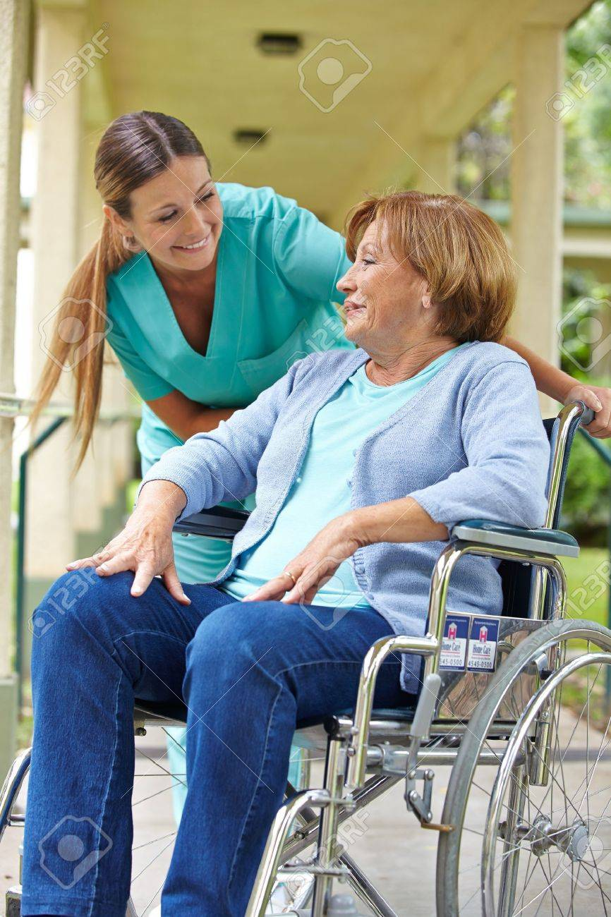 Elderly patient in wheelchair talking to nurse in a hospital garden Stock Photo - 17699359