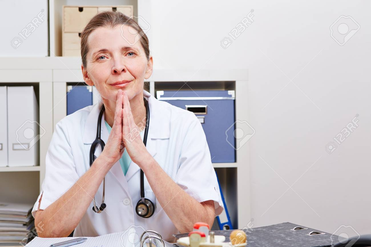 Attentive senior doctor listenint to patient in her office Stock Photo - 18185861