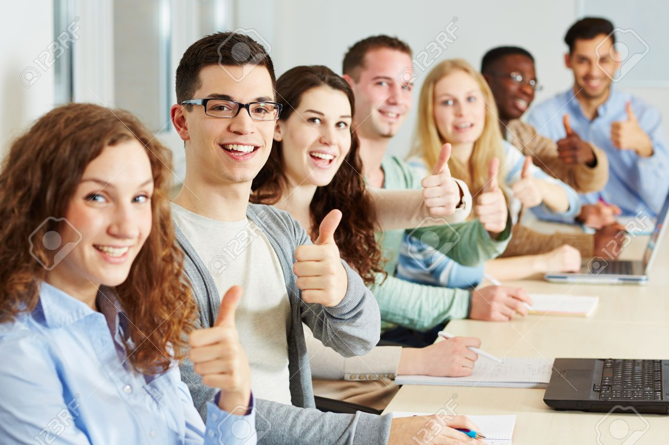 Many happy students holding their thumbs up in class Stock Photo - 18324100