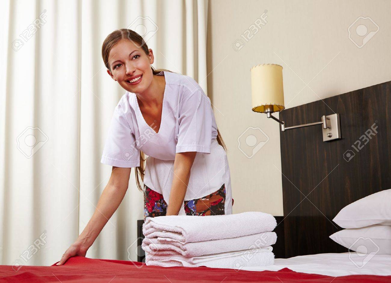 Housekeeping maid in hotel room making bed Stock Photo - 20104179