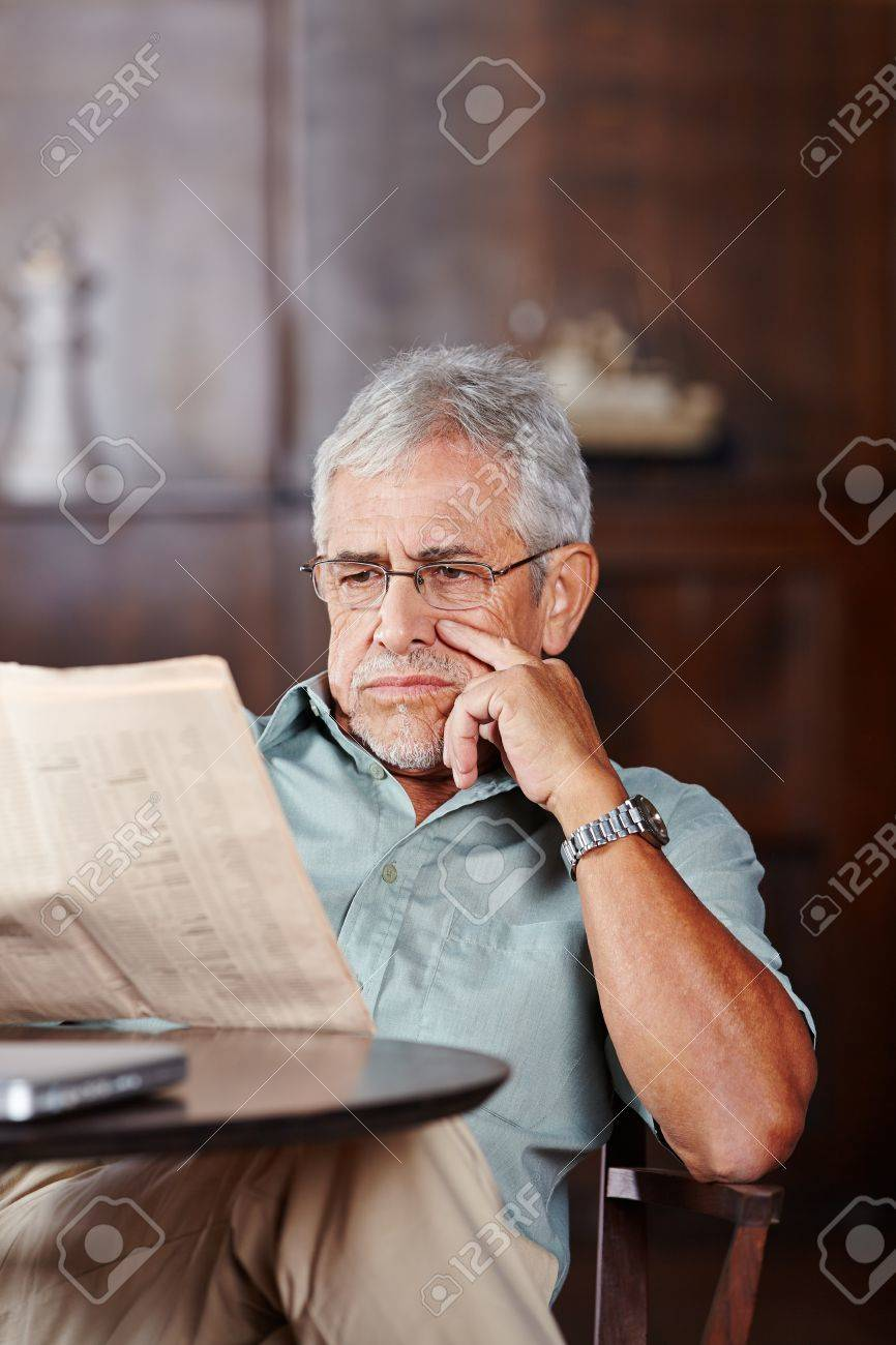 Senior man reading a newspaper at table in retirement home Stock Photo - 20104197