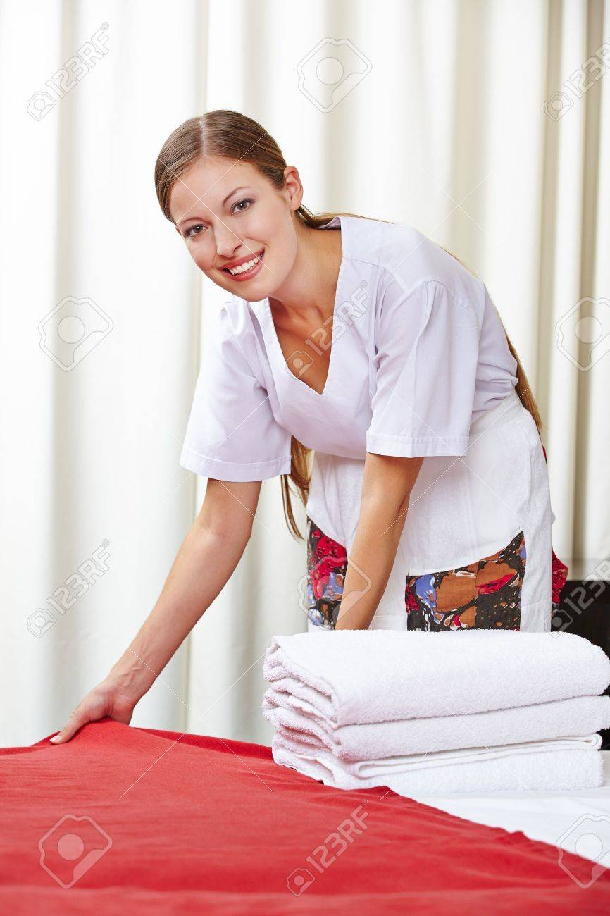 Smiling hotel maid making the bed in a hotel room Stock Photo - 20104177