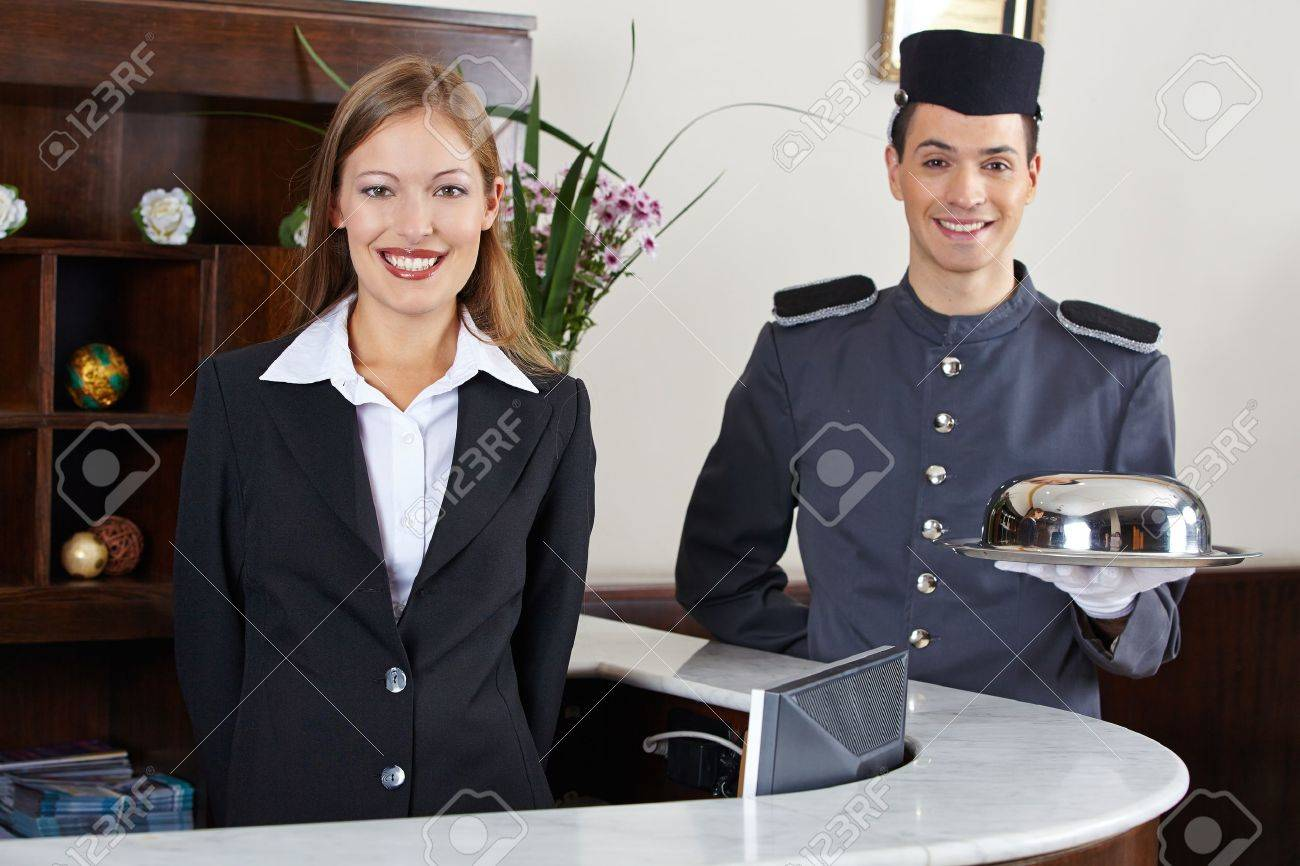 Happy concierge and receptionist in hotel waiting at counter Stock Photo - 20277901