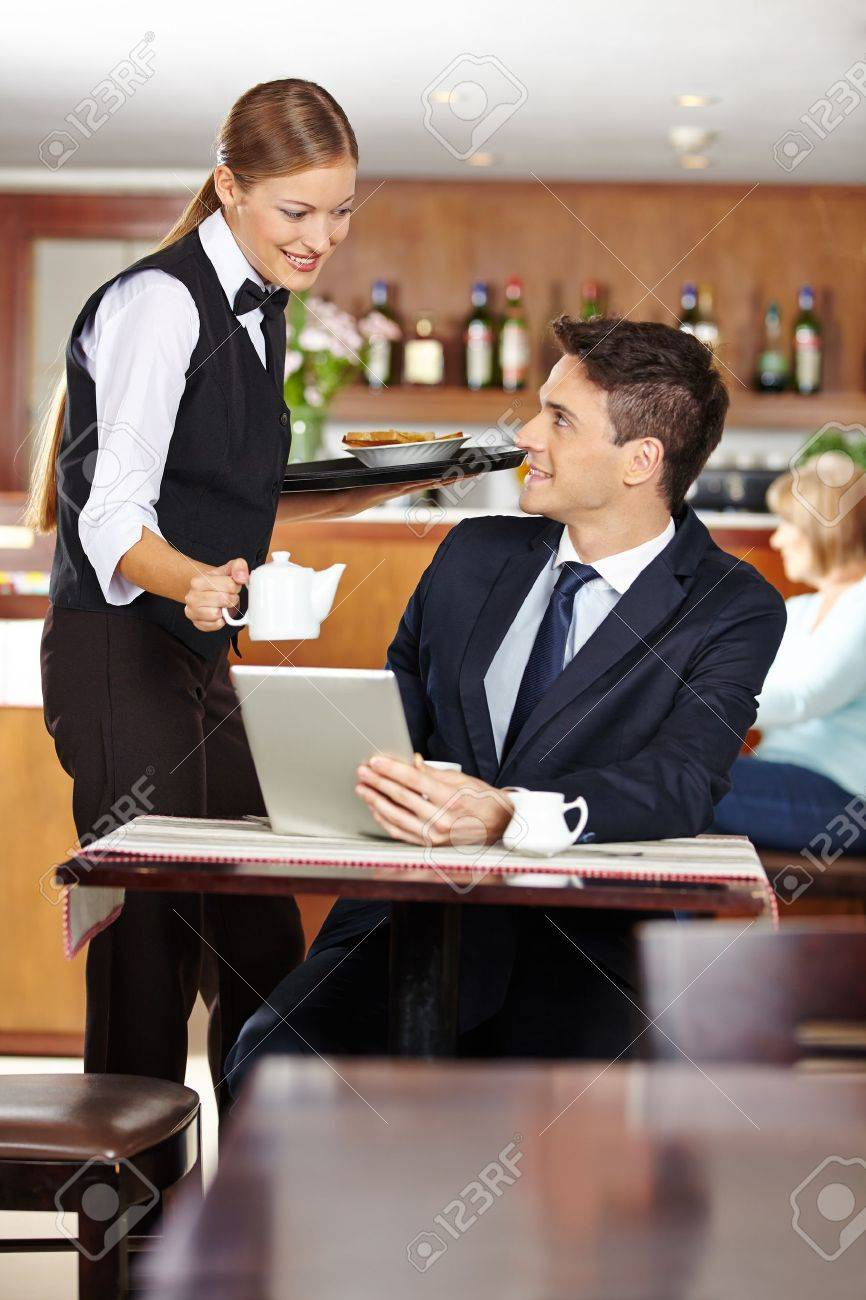female waiter serving businessman in coffee shop a pot of coffee  - female waiter serving businessman in coffee shop a pot of coffee stockphoto