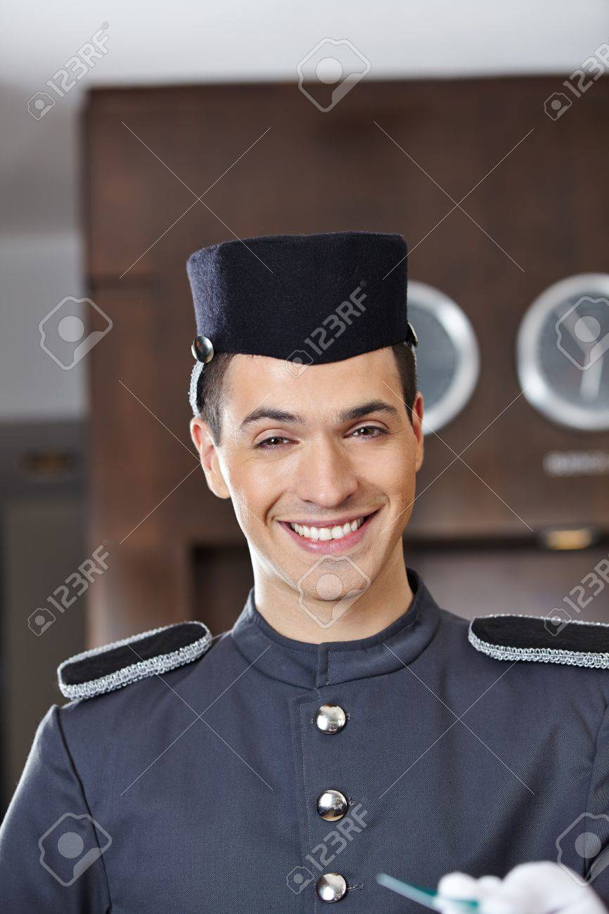 Happy hotel concierge smiling with key card in his hand Stock Photo - 20781163