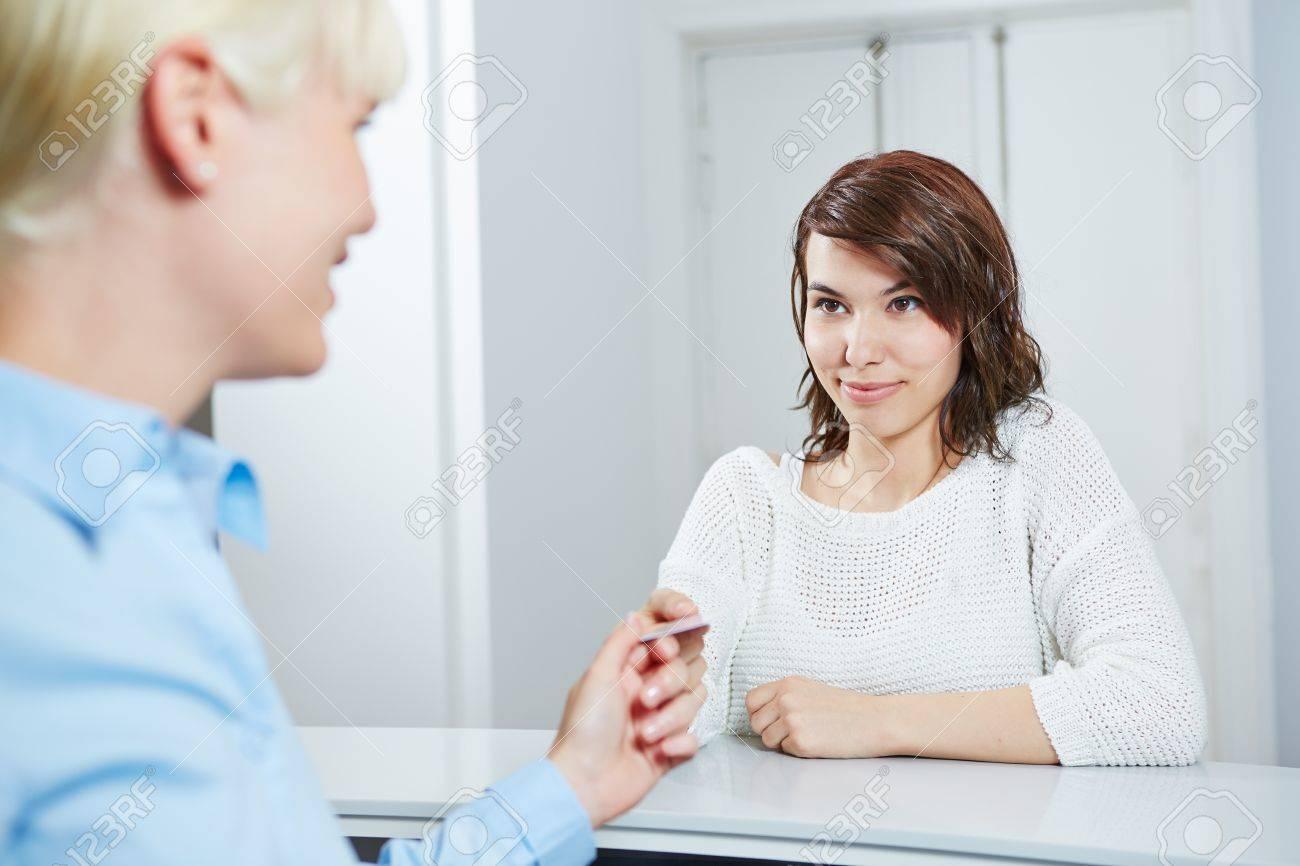 Youn femme donnant sa carte à puce de santé électronique au