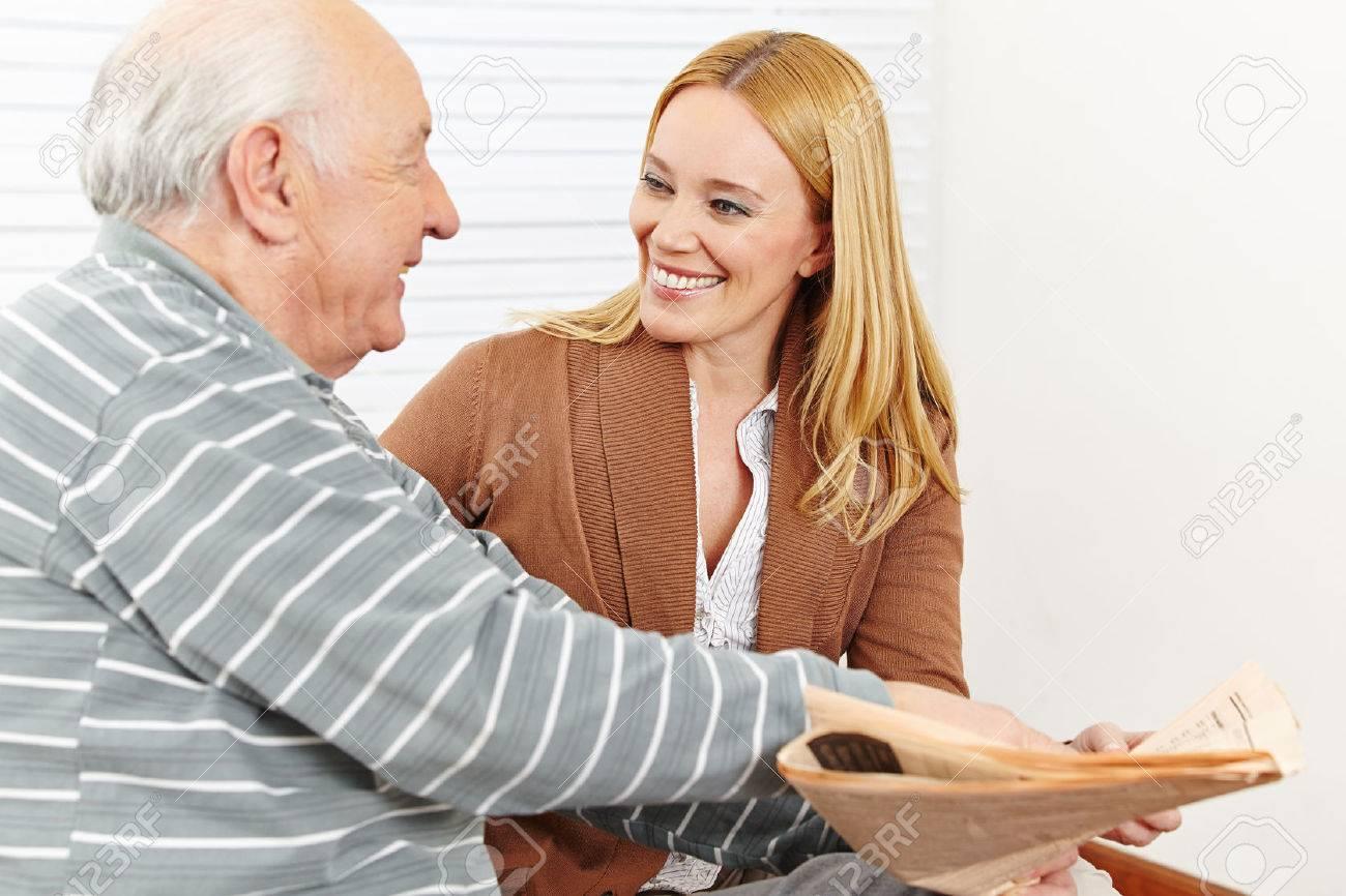 Senioren Mit Lächelnden Betreuer Frau Liest Eine Zeitung Lizenzfreie
