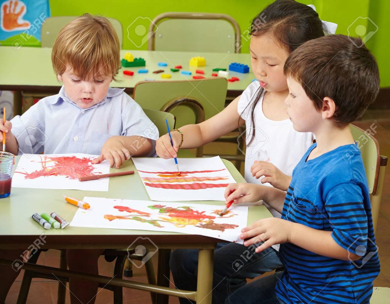 Tres Niños Pintando Con Acuarela Sobre Papel En Un Jardín De ...