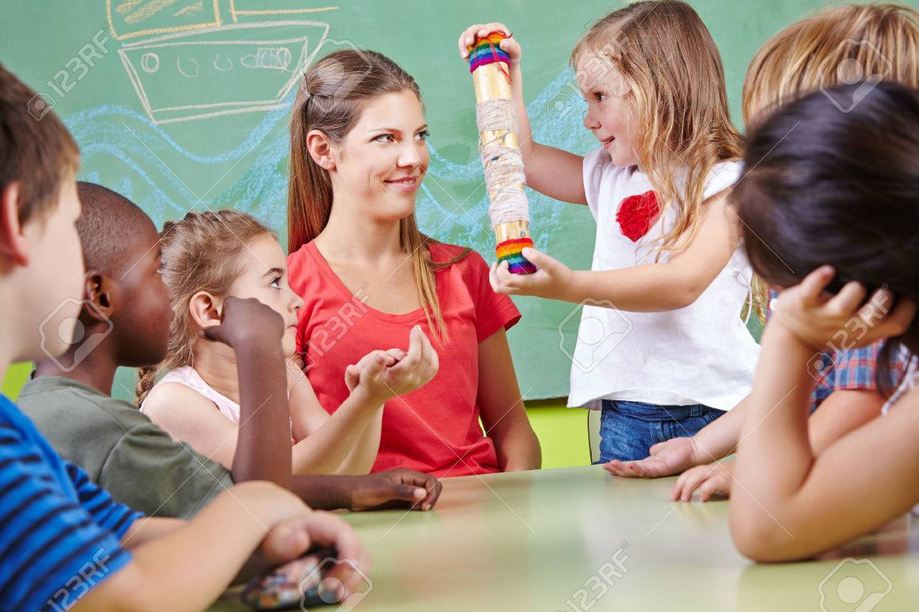 Children in musical education in kindergarten playing with rainmaker instrument Stock Photo - 26793591