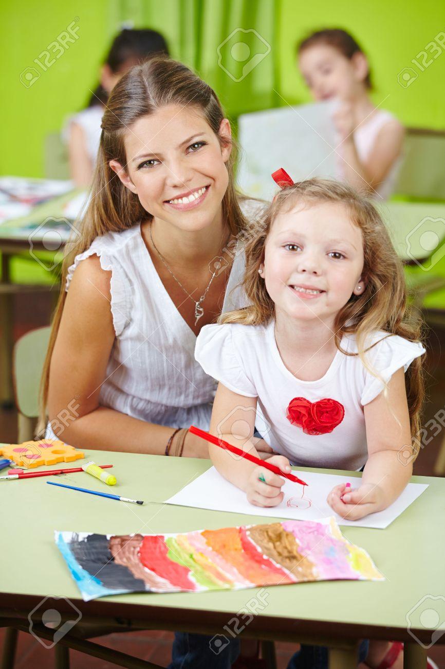 Trabajador De Cuidado De Niños Feliz Ayudando Pintura Niña En Un ...