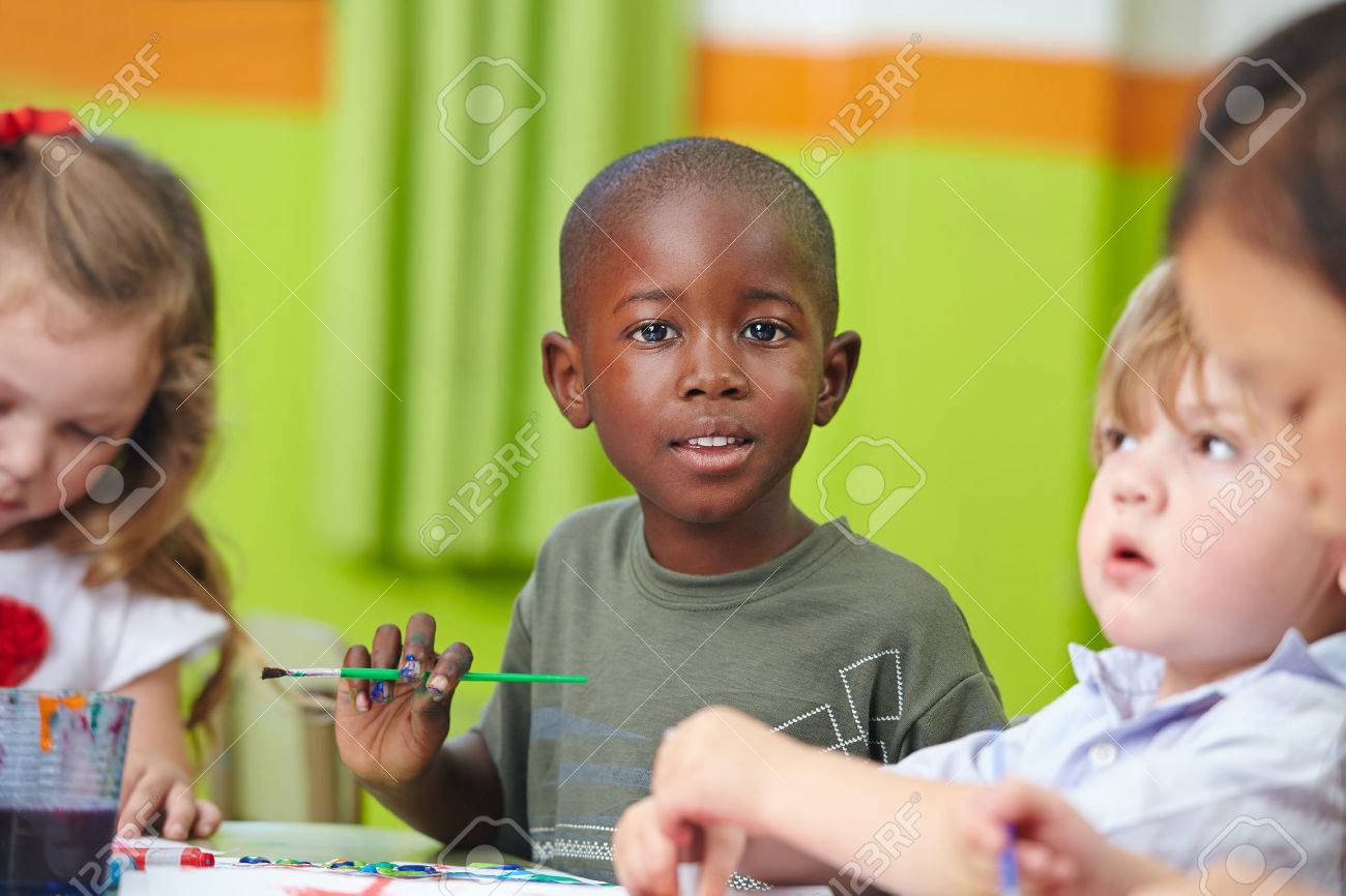 Many children in preschool painting together with brushes and color - 27574807
