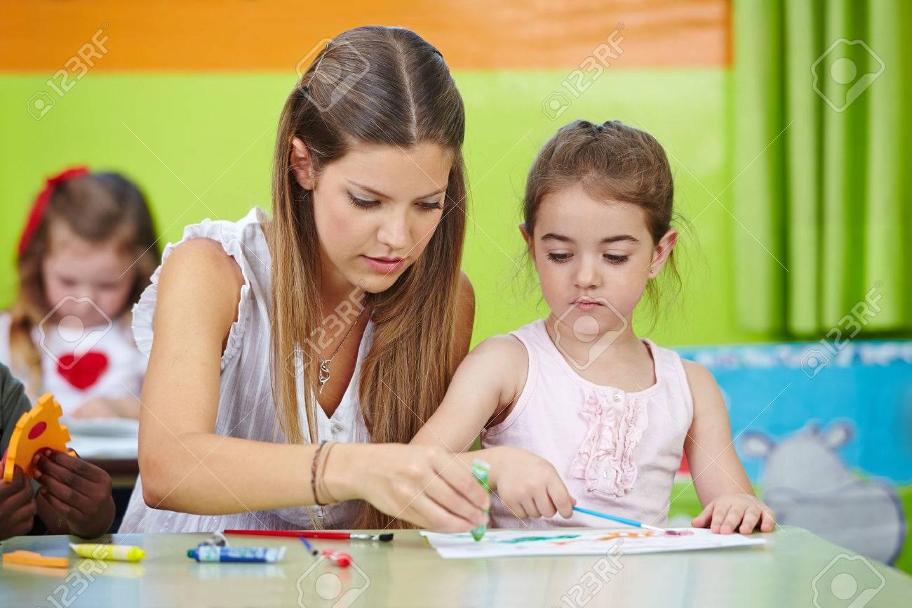 Profesor Del Cuarto De Niños Ayudando Niña Pintando Con Acuarela En ...