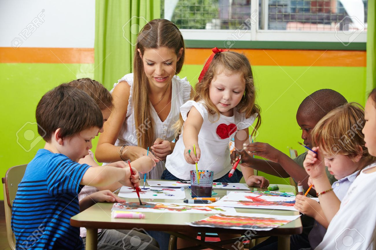 many children painting together with nursery teacher in a kindergarten - Children Painting Pictures