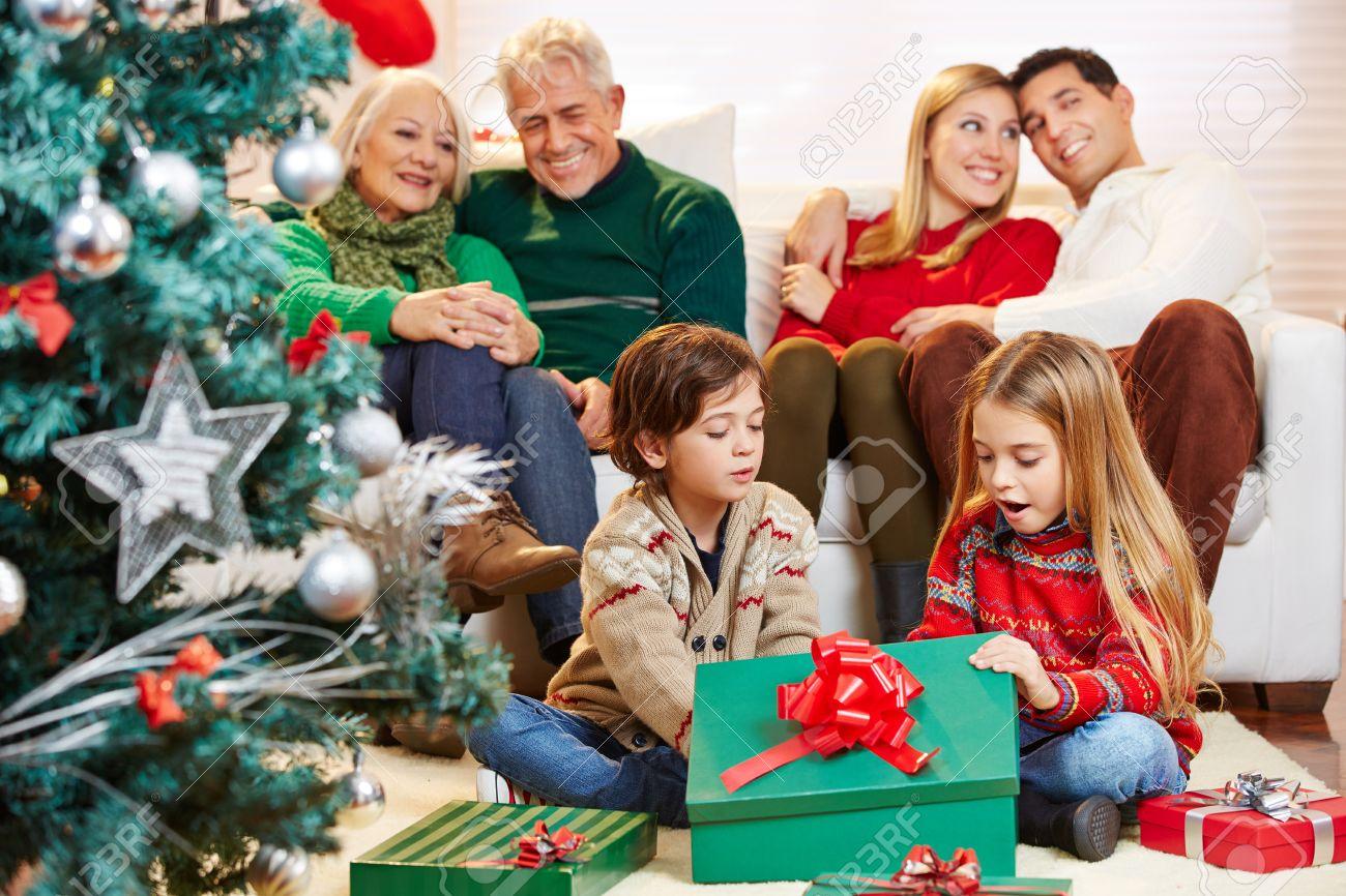 nios felices que abren los regalos en navidad mientras que los padres y los abuelos with regalos navidad padres