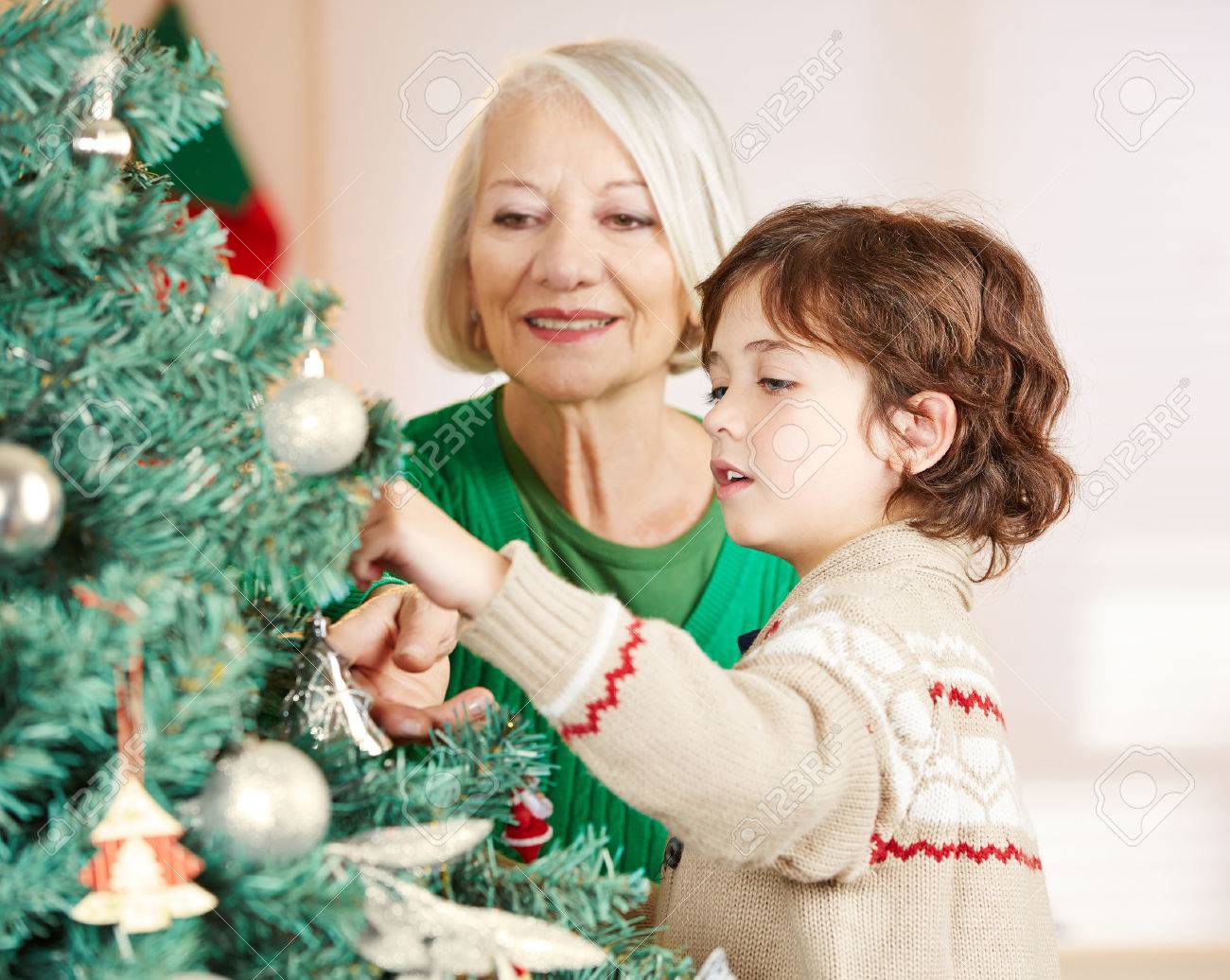grandmother and grandchild decorating christmas tree at home stock