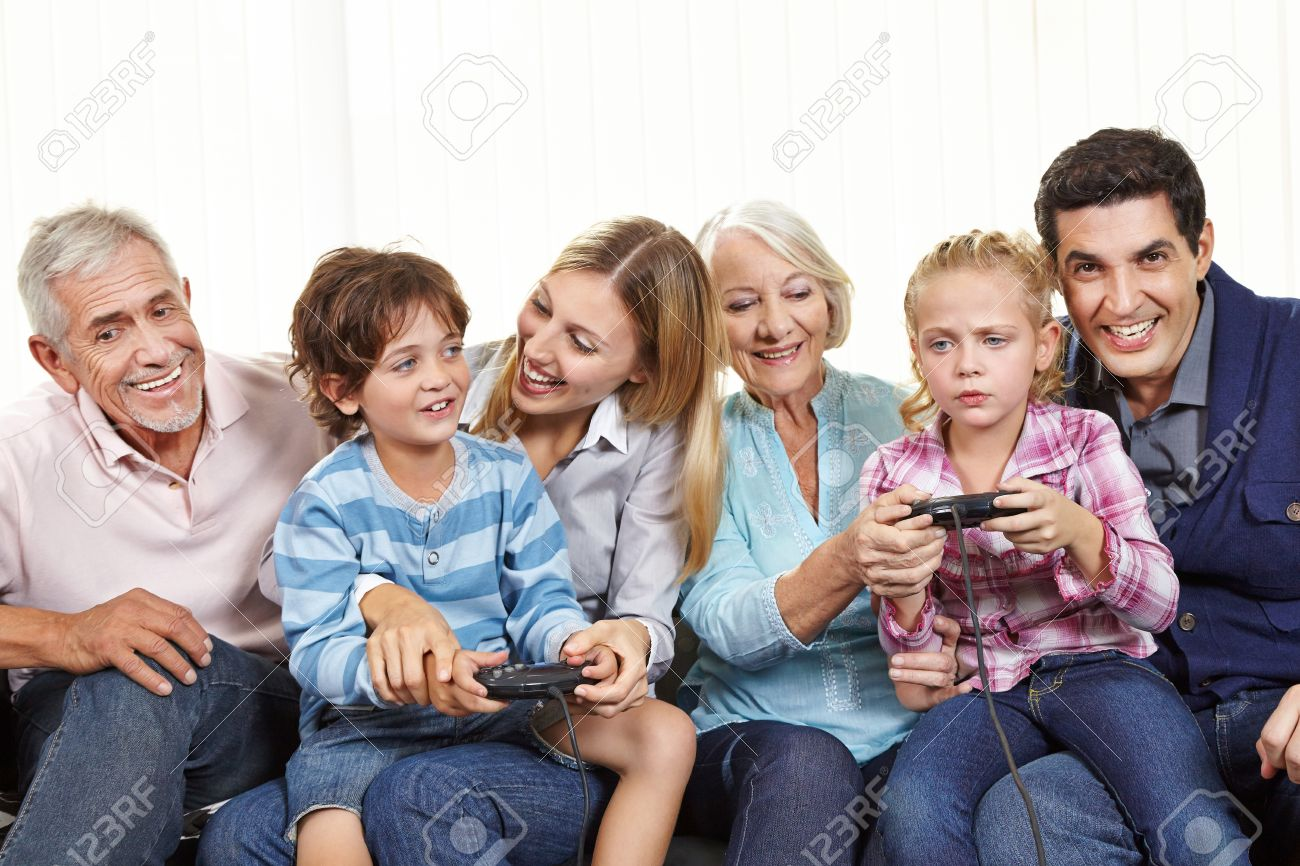 Happy Family With Controller Playing Video Games On Smart TV