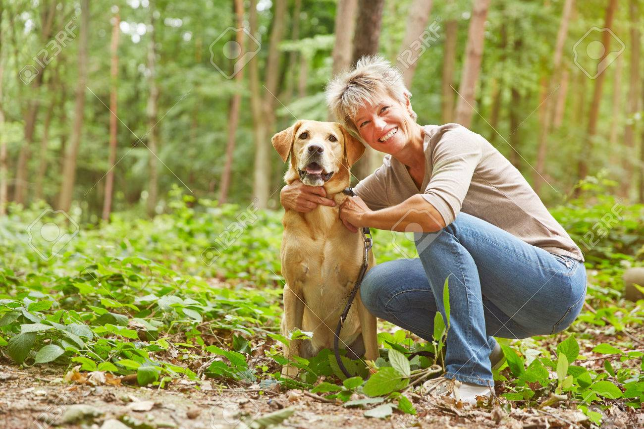 Labrador Retriever sitting with elderly woman in a forest - 32499749