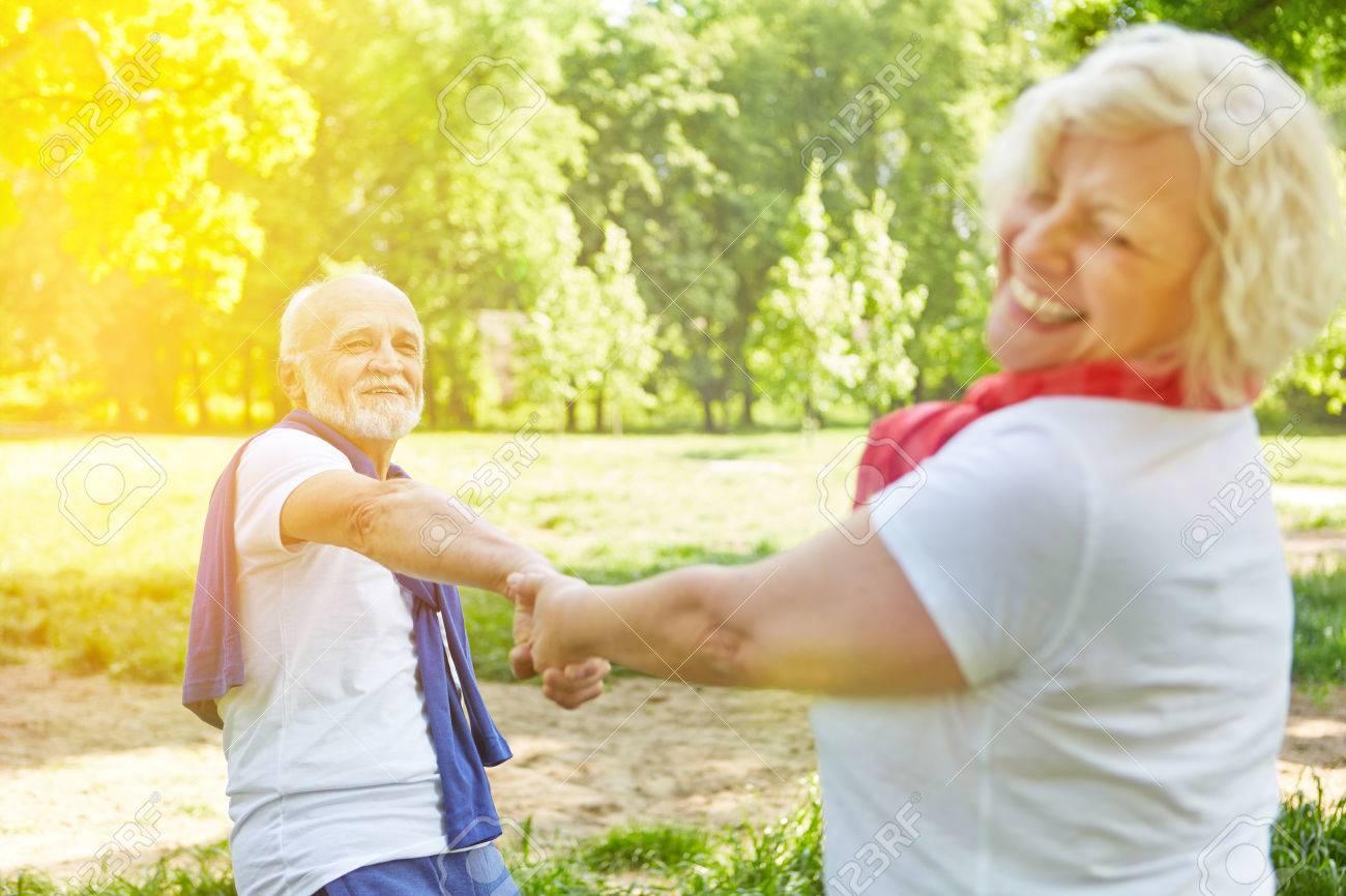 Happy senior couple dancing in a garden in sunny summer - 33552088