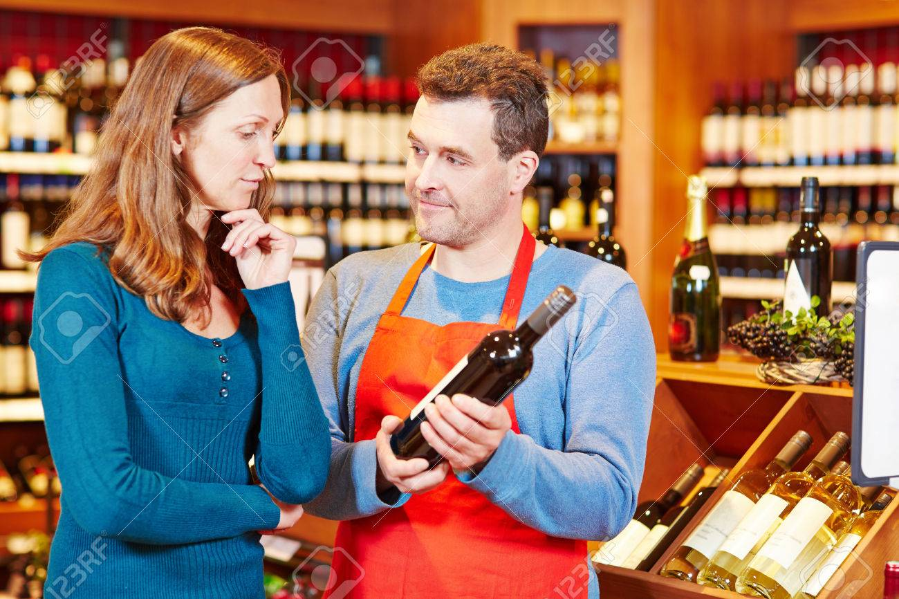 Salesman giving elderly woman advice on buying bottle of red wine - 33921121
