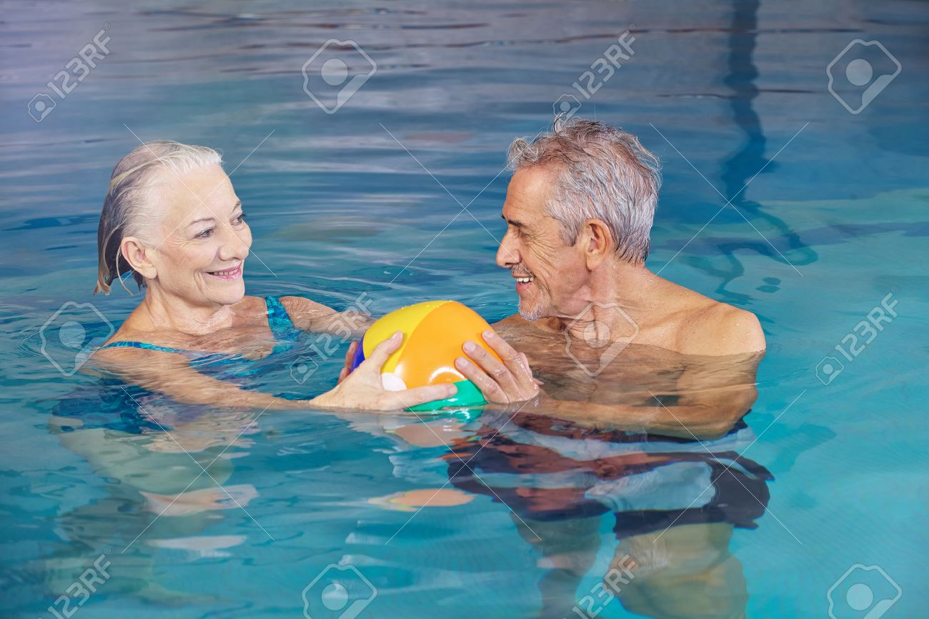 Happy senior couple playing water ball with beach ball in swimming pool Stock Photo - 38856406