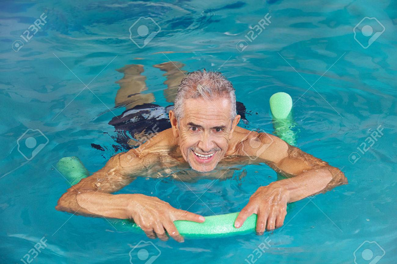 Old man swimming in water of hotel pool with swim noodle Stock Photo - 38856557