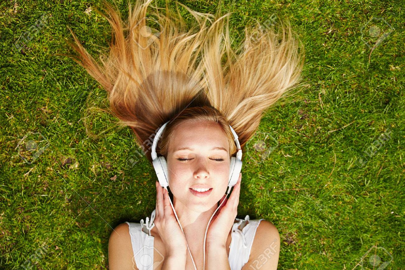 Girl listening to music streaming with headphones in summer on a meadow Stock Photo - 38856779