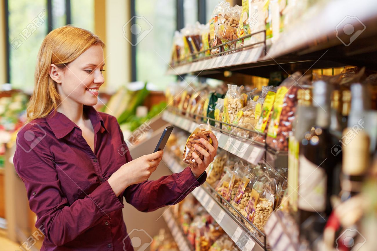 Young woman scanning barcode of bag of nuts in supermarket with her smartphone Stock Photo - 40290817