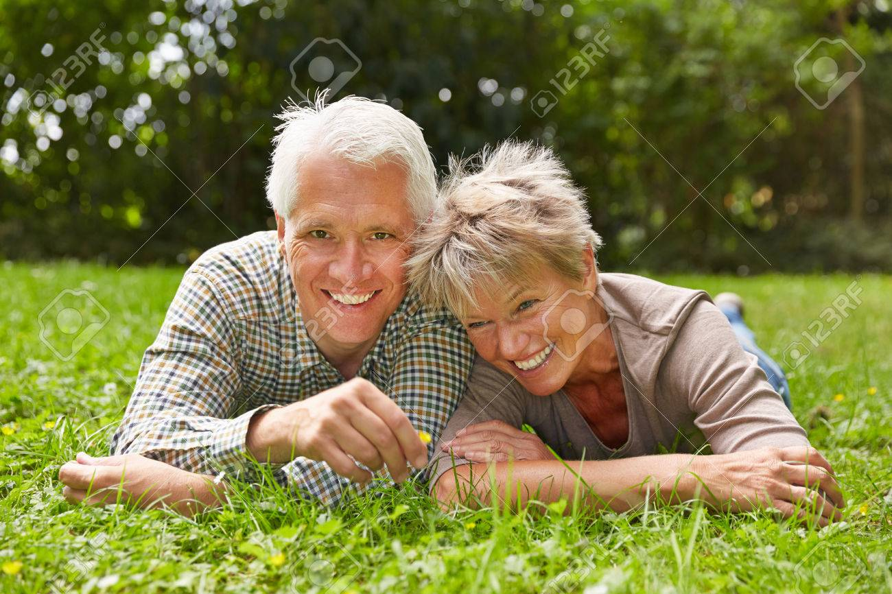 Happy senior couple laying together in grass in a meadow Stock Photo - 44326203
