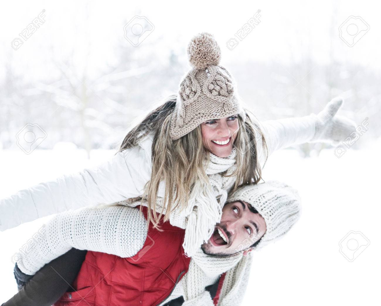 Happy man carrying smiling woman for piggyback ride in winter - 44899357
