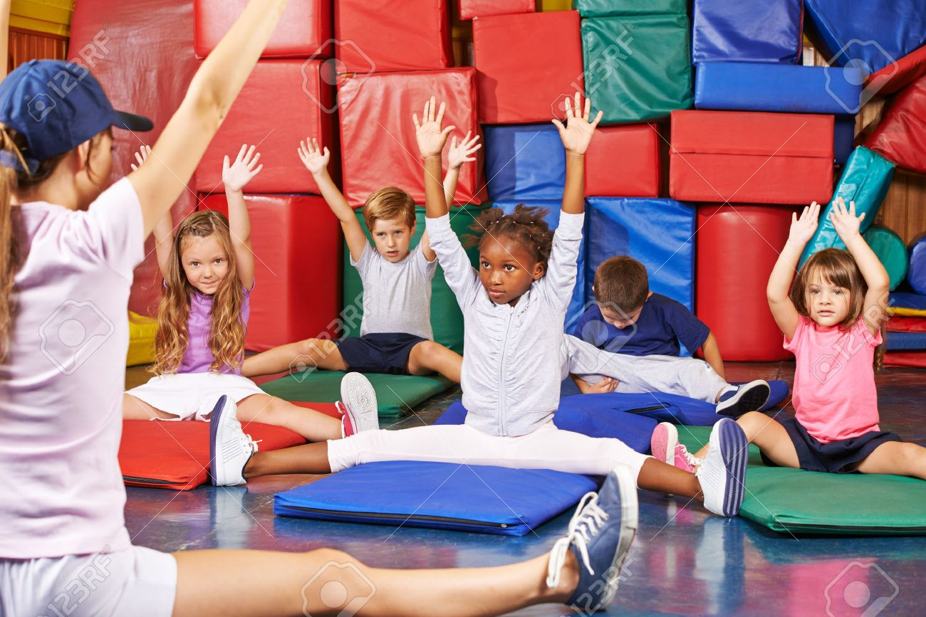 Group of children doing kids gymnastics in gym with nursery teacher Stock Photo - 47628166