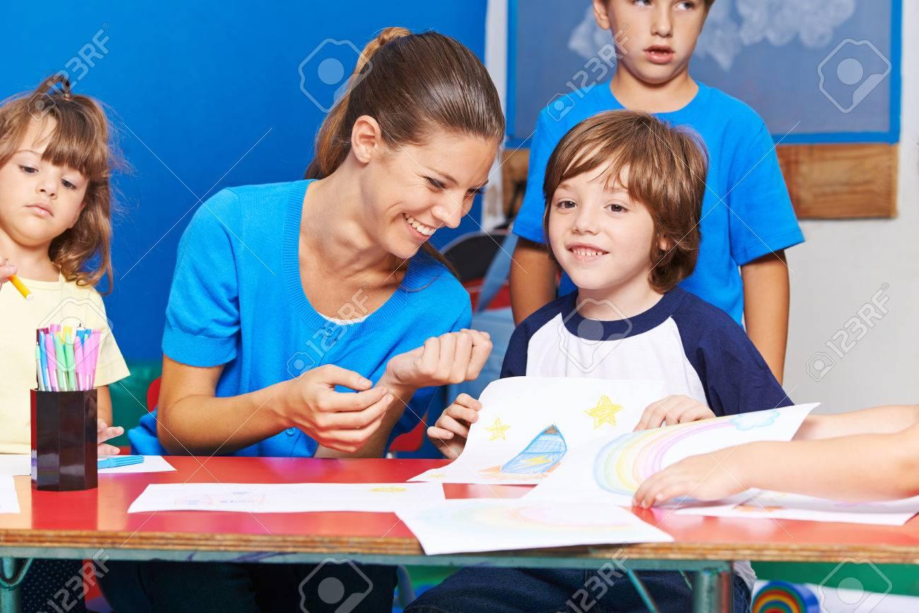Niños Felices De Dibujo Con La Sonrisa Del Profesor Guardería En El ...