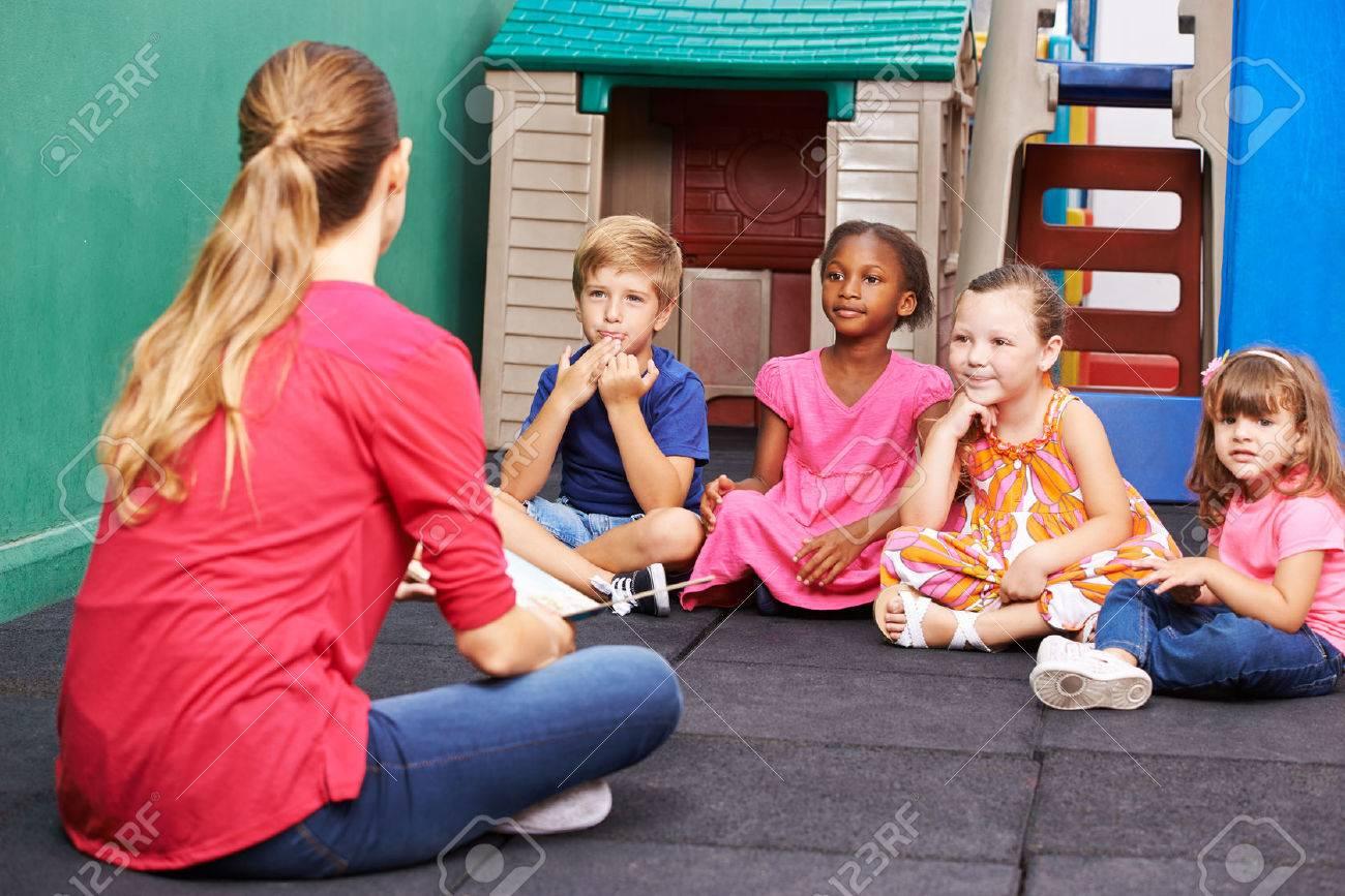 Discussion group of children in kindergarten talking to nursery teacher Stock Photo - 47629410