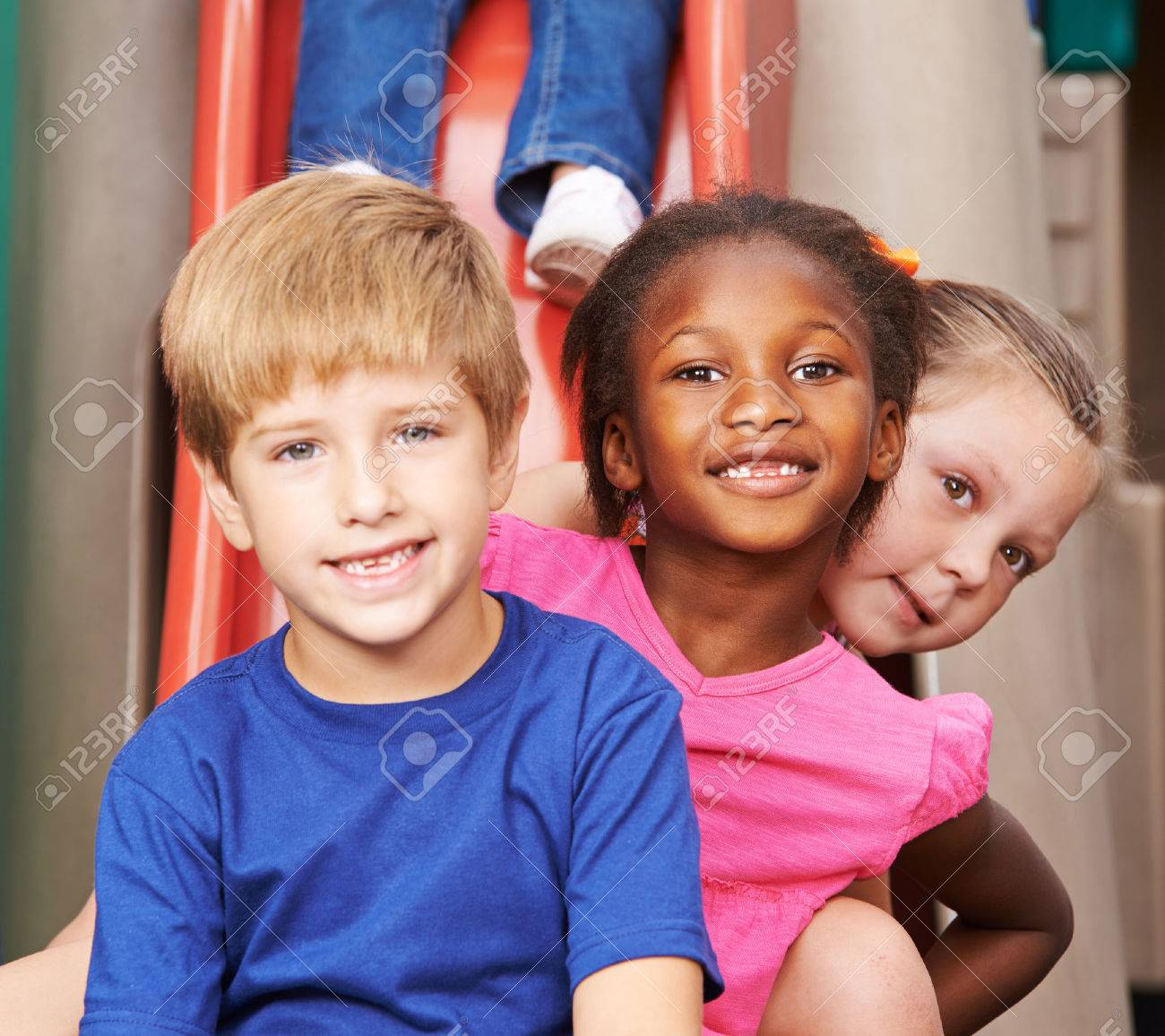 Group of children sitting behind each other on a slide in kindergarten Stock Photo - 47629412