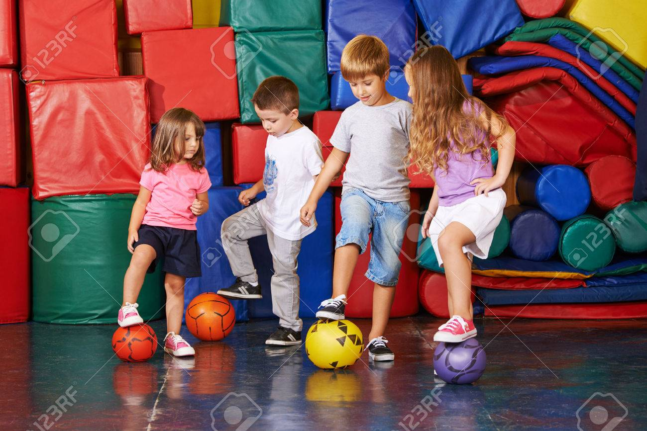 Four children playing soccer in gym of kindergarten together Stock Photo - 47629421