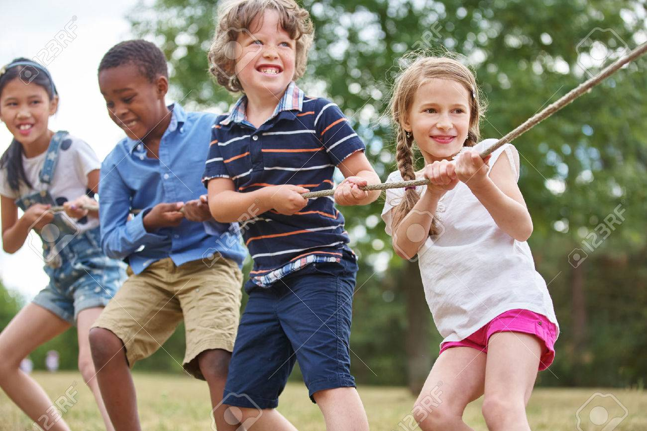 Group of kids pulling a rope at the park Stock Photo - 48658688