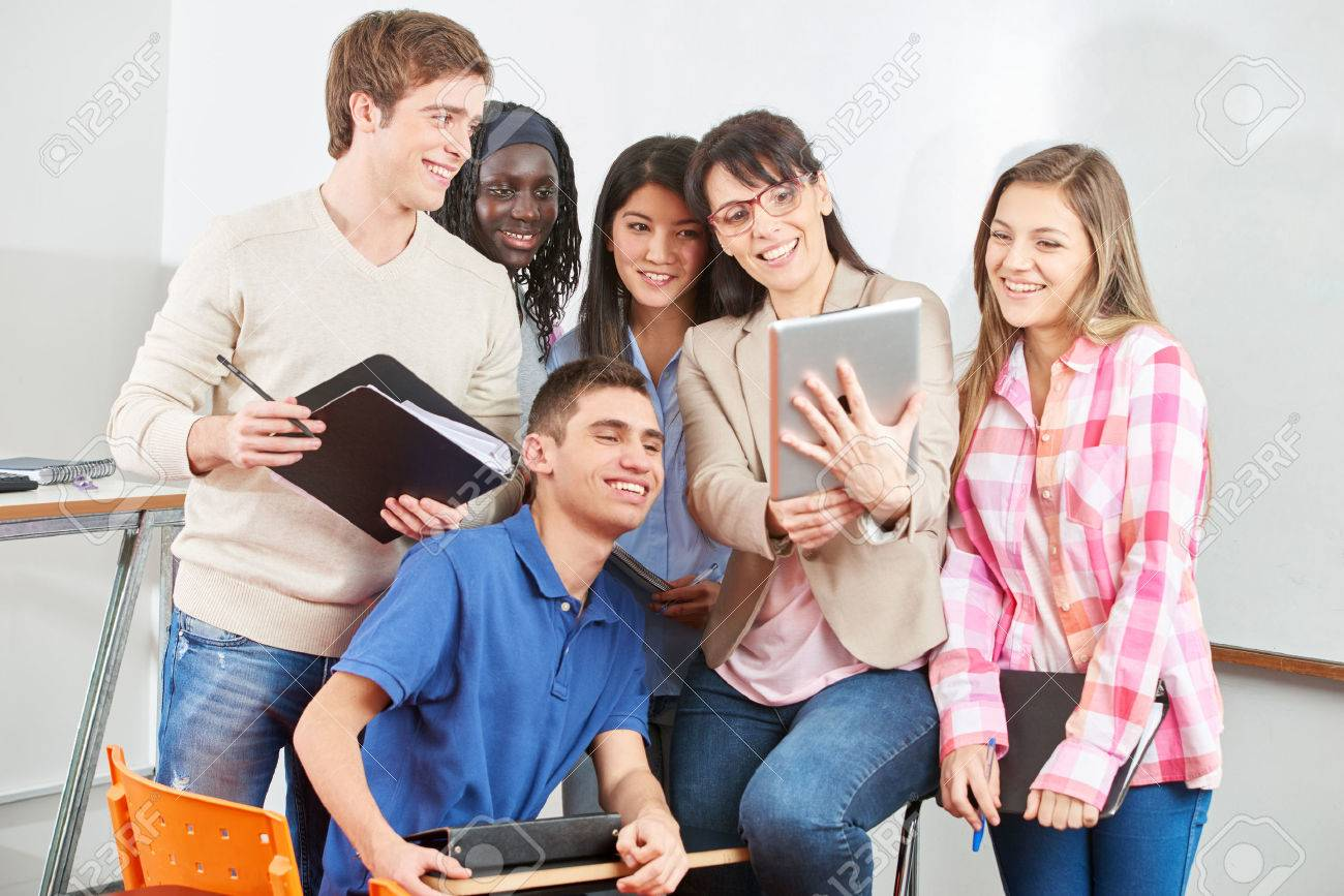 Teacher and students smiling with their tablet in class - 50909555