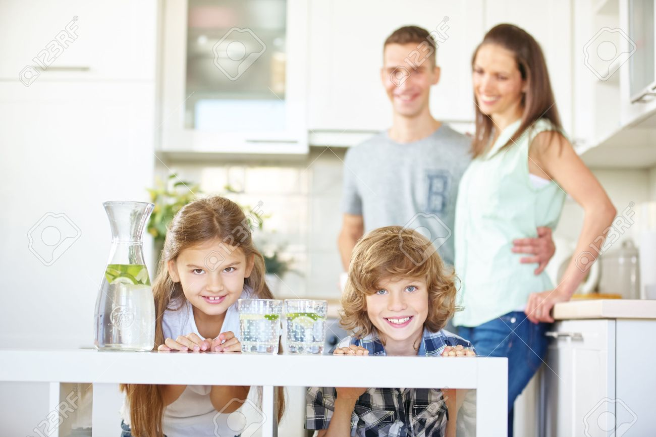 Happy family in kitchen - Happy Family And Two Children In Kitchen With Fresh Lime Water Stock Photo 52463854