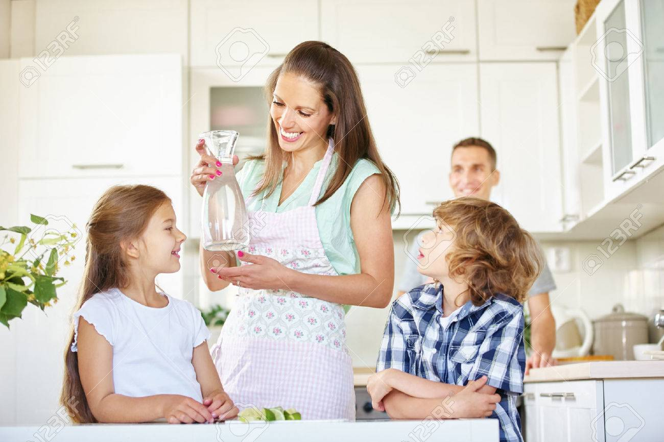 Mother and children with carafe water in the kitchen Stock Photo - 51646252