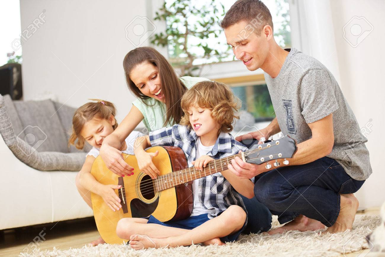 Parents and children playing guitar at home in the living room - 51646255